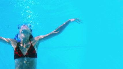 Pretty brunette swimming underwater into pool with snorkel