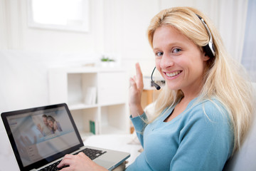 Young attractive woman blonde chatting on laptop