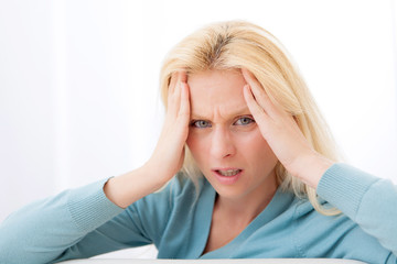 Attractive blonde woman with headache