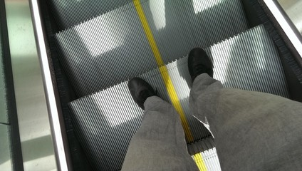 Male feet standing on metal escalator with yellow line