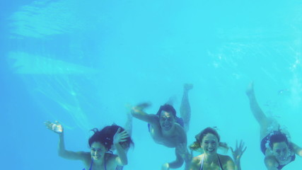 Four friends jumping into swimming pool and waving