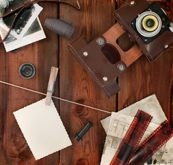Retro camera, film and photos on old wooden background