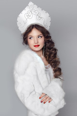 Fashion girl in fur coat and exclusive design clothes on manners