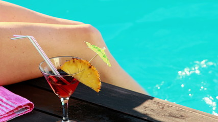 Women dangling her legs in swimming pool with cocktail