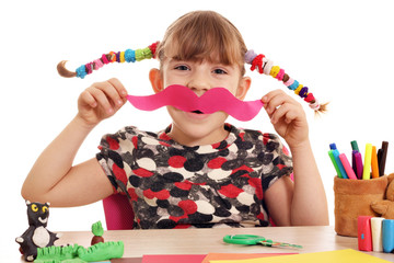happy little girl makes paper mustache