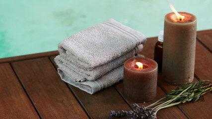 Towels candles and dried lavender by the pool