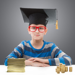 Schoolboy in a mortar board with piles of money in front of him