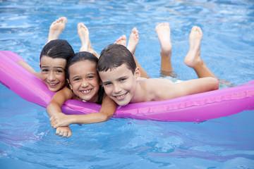 Niños en la piscina sobre colchoneta fucsia