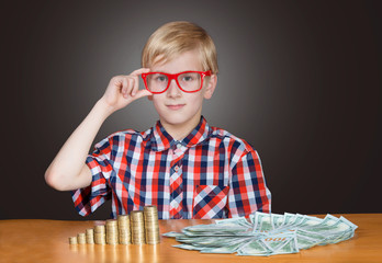 Funny boy in red-framed glasses with cash banknotes and coins