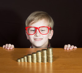 Funny boy in red-framed glasses looking at piles of coins