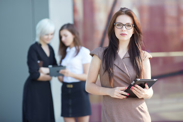 businesswomen with  tablets and phones on the street