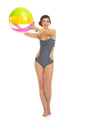 Full length portrait of happy woman in swimsuit with beach ball
