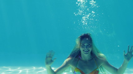 Happy blonde jumping into swimming pool and waving