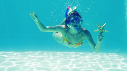 Happy blonde jumping into swimming pool wearing snorkel and hold