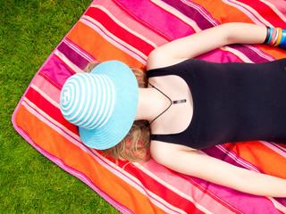 Teenage Girl with a hat covering her face lying on her back