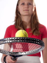 Young teenage girl holding a tennis racket and ball