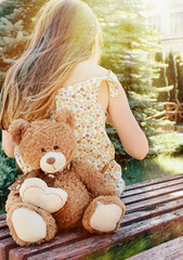 little girl sitting back with teddy bear on the bench in sun bea