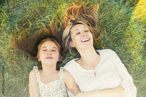 happy little girl and her mother having fun on the grass in sunn - 67537463