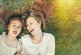cute little girl and her mother having fun on the grass in sunny poster