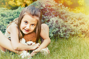 cute smiling little girl holding teddy bear and sitting on the g
