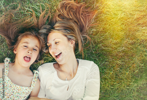 cute little girl and her mother having fun on the grass in sunny - 67537851