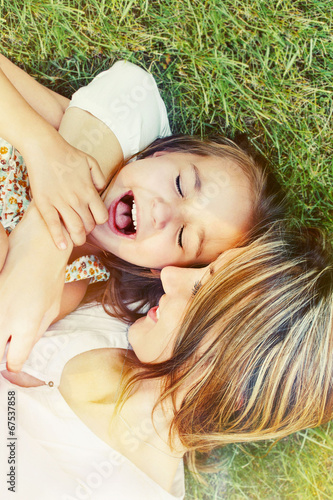 canvas print picture happy little girl and her mother having fun outdoors on the gras