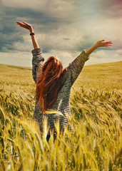 young red hair woman standing back hands up to breathtaking view