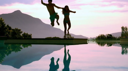 Couple jumping into swimming pool holding hands