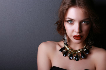 Portrait of young beautiful brunette woman in ear-rings, beads