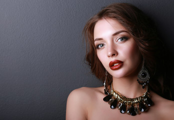 Young beautiful brunette woman in ear-rings, beads