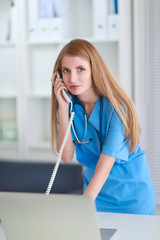 Medical doctor woman with computer and telephone.
