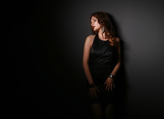 Portrait of beautiful brunette woman in black dress.