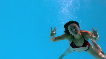 Happy brunette waving at camera underwater in swimming pool