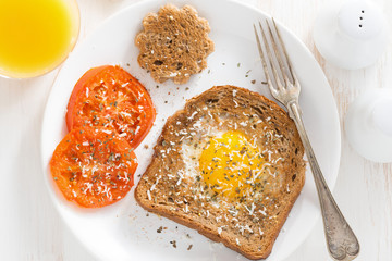 fried egg in toast and grilled tomatoes for breakfast, top view