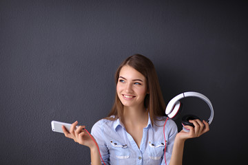 Smiling girl with headphones isolated on grey background