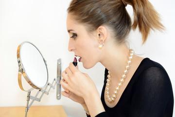 Frau benutzt Lippenstift vor Schmink-Spiegel