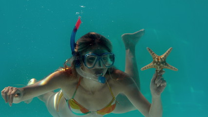 Woman wearing snorkel holding starfish underwater