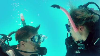 Couple in scuba gear looking at each other underwater