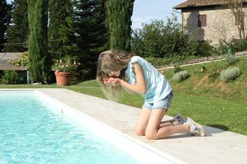 Bambina raccoglie acqua dal bordo di una piscina