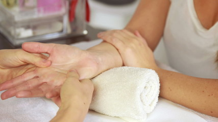 Beauty therapist massaging customers hand