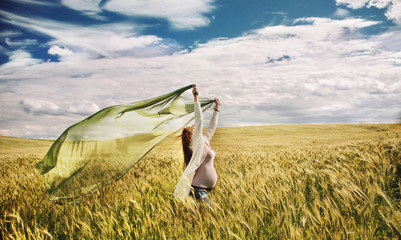 healthy pregnant happy woman feeling freedom of nature in windy