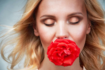sensual tender young woman portrait with breeze hair and rose in