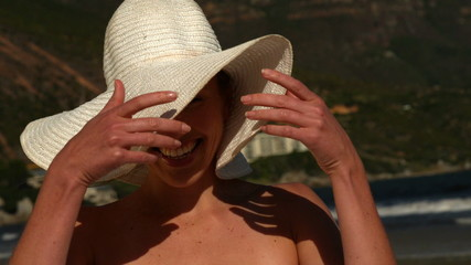 Smiling blonde moving her sunhat off her face on the beach