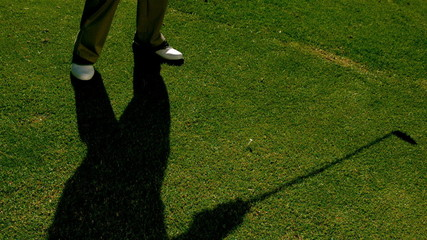 Golfer hitting the golf ball with club on the course