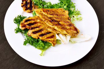Grilled chicken breast, on a bed of lettuce.