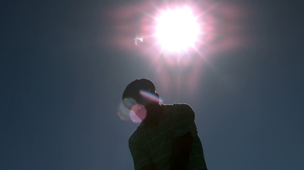 Golfer taking a swing under the sun