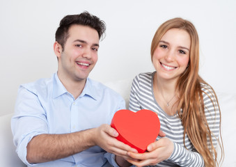 Laughing young love couple with a gift