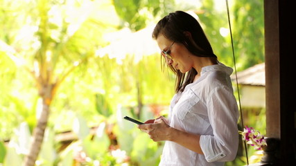 Young woman texting on smartphone on country house terrace