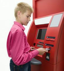 Мальчик вставляет карту в банкомат