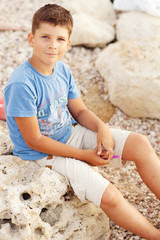 Small boy sitting on the beach looking at the camera